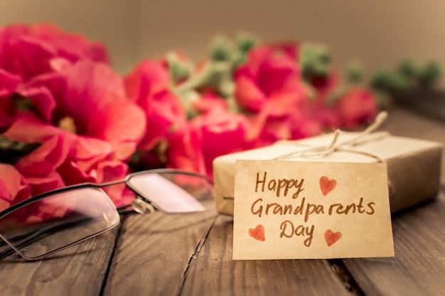 Urocza kartka z czerwonymi kwiatami, okularami, pudełkiem prezentowym i metką rzemieślniczą.