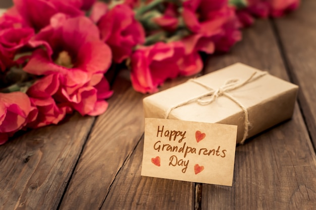 Urocza kartka z czerwonymi kwiatami, pudełkiem prezentowym i metką rzemieślniczą.