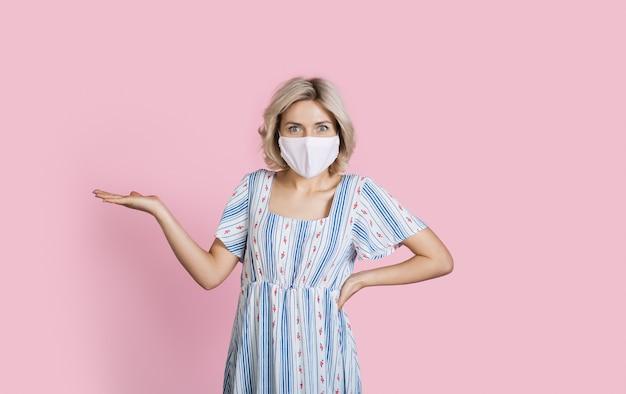 Urocza kaukaska blondynka reklamująca coś z maską medyczną na twarzy na różowej ścianie studia z wolną przestrzenią, gestykulująca dłonią