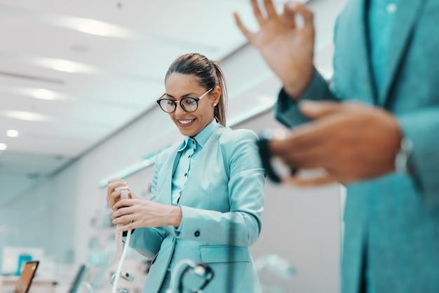 Urocza kaukaska brunetka w stroju wizytowym i okularach uśmiechnięta i patrząca na zegarek, który chce kupić. na pierwszym planie niewyraźne człowiek pokazujący znak porządku. wnętrze sklepu technicznego.