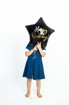 Urocza kaukaska dziewczynka zakrywa twarz czarnym żelowym balonem z napisem happy birthday. zdjęcie w studio na białym tle