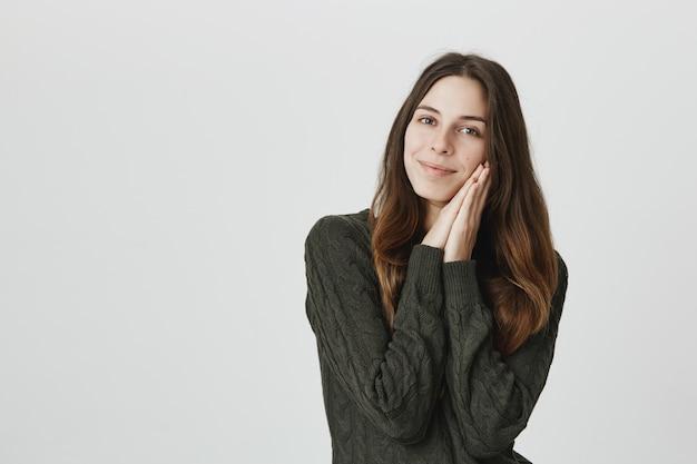 Urocza kaukaska kobieta z delikatnym uśmiechem, oparta na dłoniach, dotyka miękkiej, czystej skóry