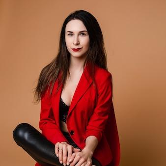 Urocza kaukaska kobieta z długimi ciemnymi prostymi włosami w czerwono-czarnym garniturze biurowym, czarne buty siedzi na czerwonym krześle