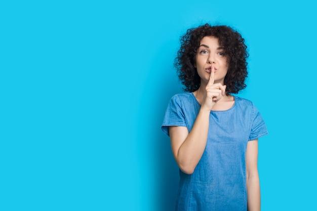 Urocza kaukaska kobieta z kręconymi włosami, wskazująca na znak ciszy, pozując na niebieskiej ścianie z pustą przestrzenią