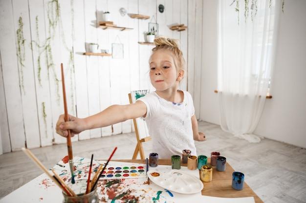 Urocza kaukaska mała kreatywna i utalentowana dziewczyna trzymająca w dłoni duży pędzel i zanurzająca go w wodzie, stojąca za biurkiem w pokoju sztuki.
