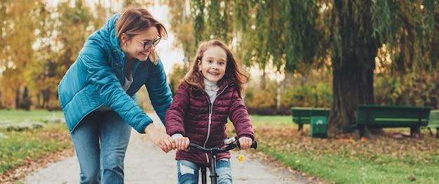 Urocza kaukaska matka uczy swoją małą dziewczynkę nurkować na rowerze w parku