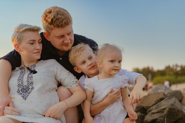 Urocza kaukaska rodzina z mamą spodziewającą się dziecka cieszyć się zachodem słońca na plaży