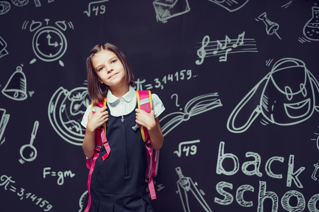 Urocza kaukaska uczennica przygotowuje się do pójścia do szkoły z plecakiem z przodu, z powrotem do szkoły