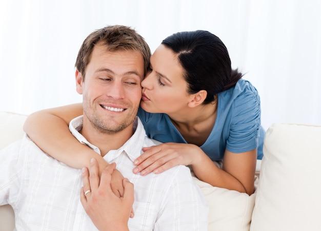Urocza kobieta całuje jej chłopaka podczas gdy relaksujący na kanapie