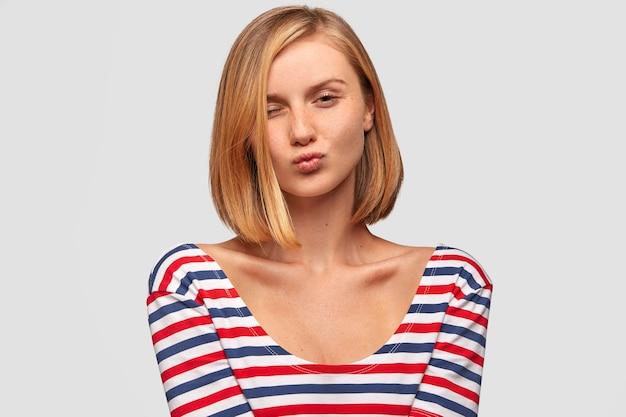 Urocza kobieta flirtuje z chłopakiem, wydyma usta i mruga, ma atrakcyjny wygląd i modną fryzurę, nosi jasną kurtkę w paski