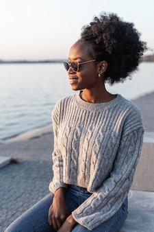 Urocza kobieta jest ubranym okulary przeciwsłonecznych i patrzeje daleko od