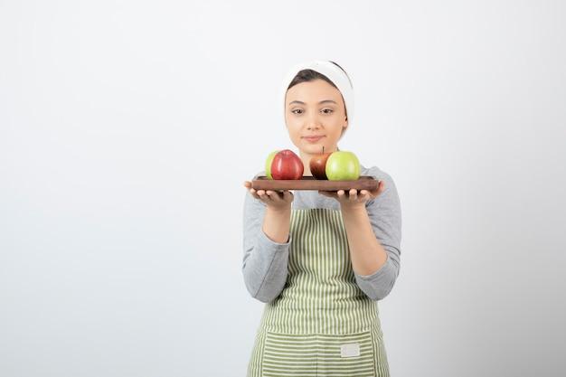 Urocza kobieta kucharz trzymając talerz jabłek na białym tle.