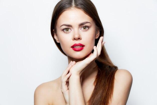 Urocza kobieta nagie ramiona ręce w pobliżu twarze czerwone usta atrakcyjny wygląd jasny makijaż
