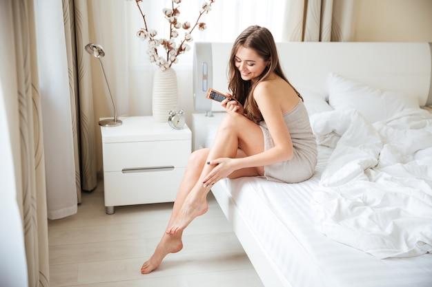 Urocza kobieta nakłada krem na nogi na łóżku w domu