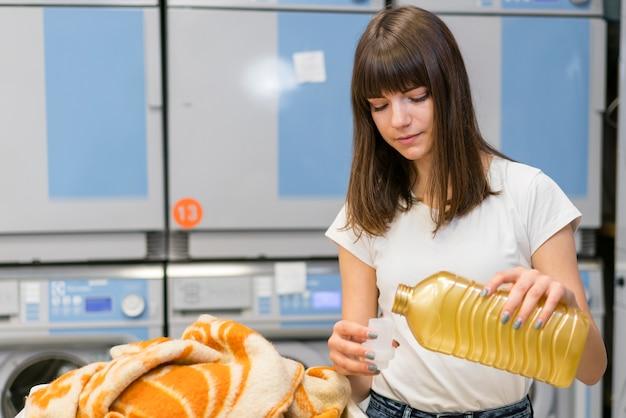 Urocza kobieta nalewająca detergent w nakrętce