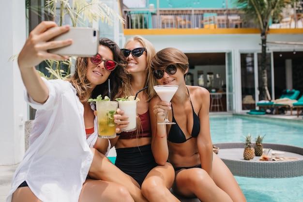 Urocza kobieta o ciemnych włosach, trzymając koktajl i robiąc selfie. piękne kobiety chłodzą się w basenie i pozują do zdjęcia.