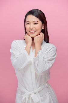 Urocza kobieta o czystej skórze, uśmiechająca się z białymi zębami, trzymająca ręce pod brodą na różowym tle