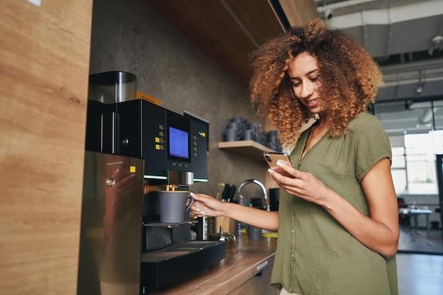 Urocza Kobieta Patrząca Na Telefon I Pijąca Kawę Premium Zdjęcia