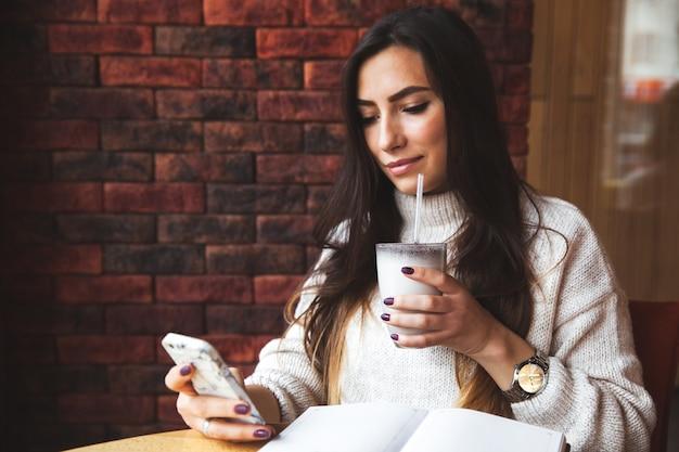 Urocza kobieta patrzy na telefon w kawiarni. smaczne ciasto czekoladowe i kawa na stole. jasny słoneczny poranek w kawiarni