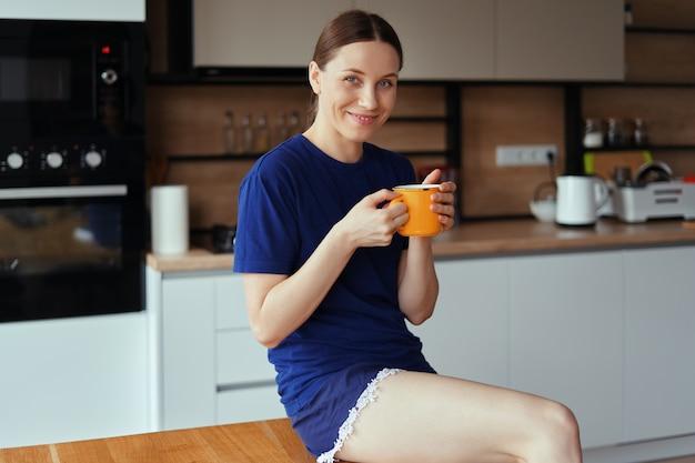 Urocza kobieta pije filiżankę herbaty w kuchni