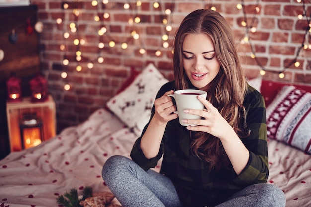Urocza kobieta pije kawę w swojej sypialni