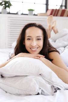 Urocza kobieta pozuje kłamać na łóżku