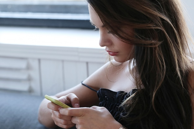 Urocza kobieta pozuje texing na jej telefonie