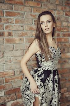 Urocza kobieta pozuje z elegancką czerni suknią, mody pojęcie