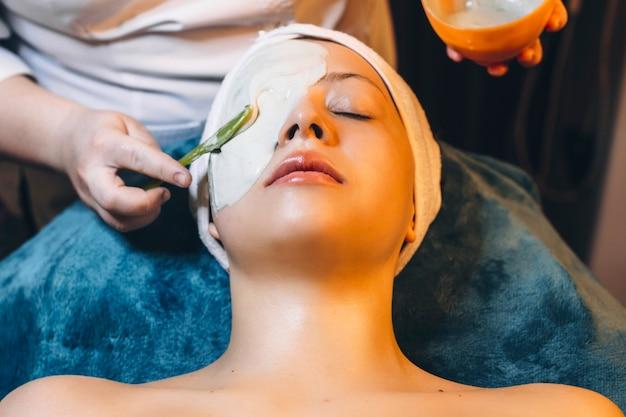 Urocza kobieta robi maskę alginatową w centrum odnowy biologicznej.