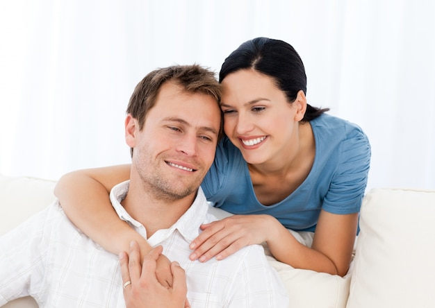 Urocza kobieta ściska jej chłopaka podczas gdy relaksujący na kanapie