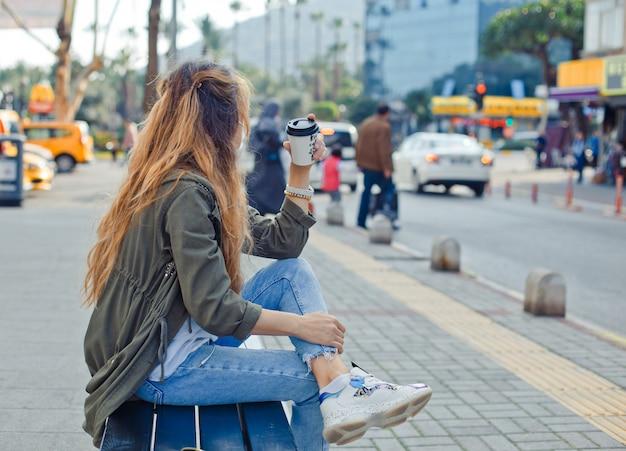 Urocza kobieta siedząca na ławce z kawą, myśląca na ulicy w ciągu dnia.