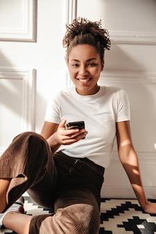 Urocza kobieta siedzi na podłodze z smartphone