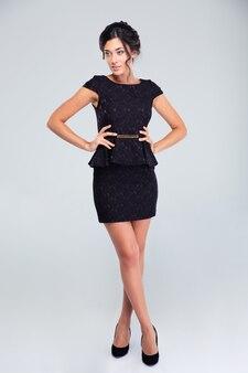 Urocza kobieta stojąca w czarnej sukni