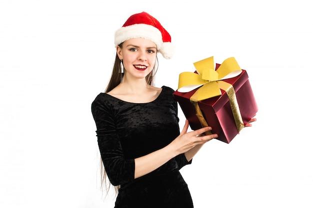 Urocza kobieta trzyma bożenarodzeniowego prezent i ono uśmiecha się