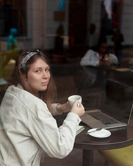 Urocza kobieta trzyma filiżankę kawy