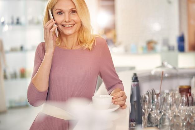 Urocza kobieta trzymająca uśmiech na twarzy podczas rozmowy przez telefon, stojąca przy ladzie