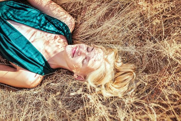 Urocza kobieta ubrana w niebieską elegancką sukienkę, leżącą na polu pszenicy