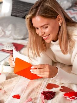 Urocza kobieta uśmiecha się do koperty