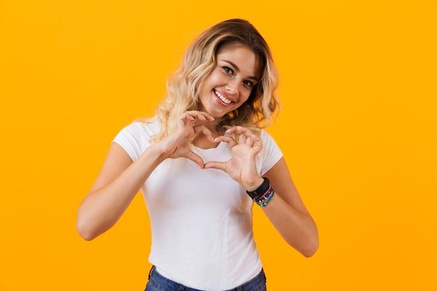 Urocza kobieta uśmiecha się i pokazuje kształt serca palcami, na białym tle nad żółtą ścianą