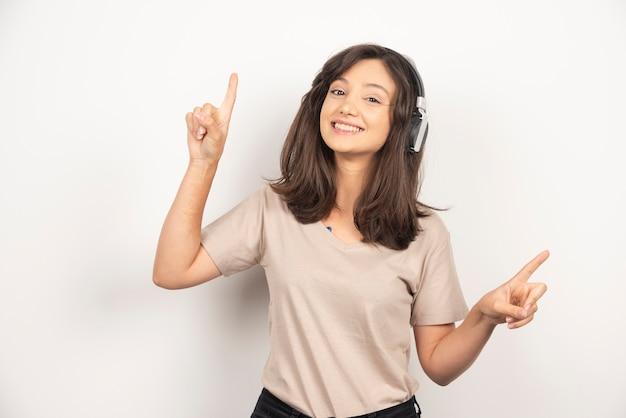 Urocza kobieta w beżowej koszuli, zabawy podczas słuchania muzyki za pomocą słuchawek bezprzewodowych na białym tle.