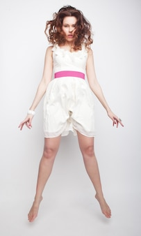 Urocza kobieta w białej sukni skaczącej na szarym tle
