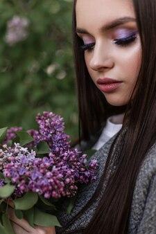 Urocza kobieta w chustce w modne ubrania z makijażem z bukietem niesamowitych świeżych fioletowych kwiatów stoi w pobliżu zielonych liści w parku. urocza dziewczyna patrzy na bukiet i cieszy się pięknem i zapachem bzu.