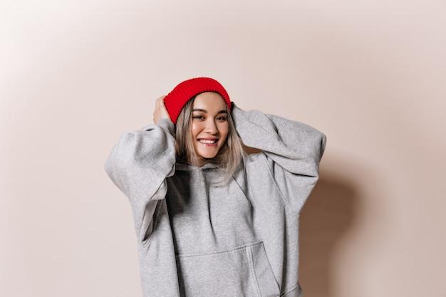 Urocza kobieta w czerwonej czapce i bluzie uśmiechnięta na odosobnionej ścianie