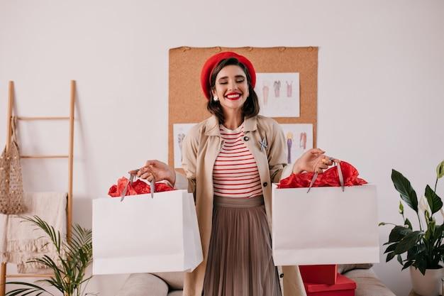 Urocza kobieta w czerwonym berecie trzymając białe torby na zakupy. szczęśliwa wspaniała dziewczyna z pięknym uśmiechem w jesiennym beżowym płaszczu pozowanie.