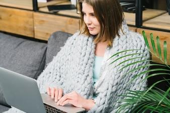 Urocza kobieta w koc przegląda laptop
