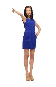 Urocza kobieta w niebieskiej sukience wskazując palcem