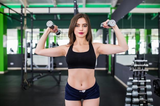 Urocza kobieta w nowoczesnej czarnej odzieży sportowej o sportowym silnym ciele