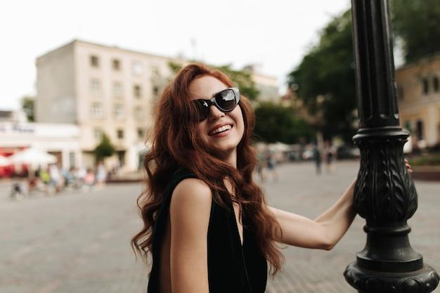 Urocza kobieta w okularach przeciwsłonecznych z uśmiechem