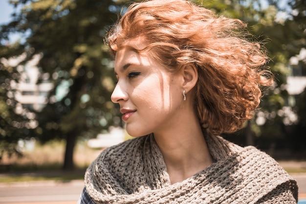 Urocza kobieta w parku na wietrznym dniu