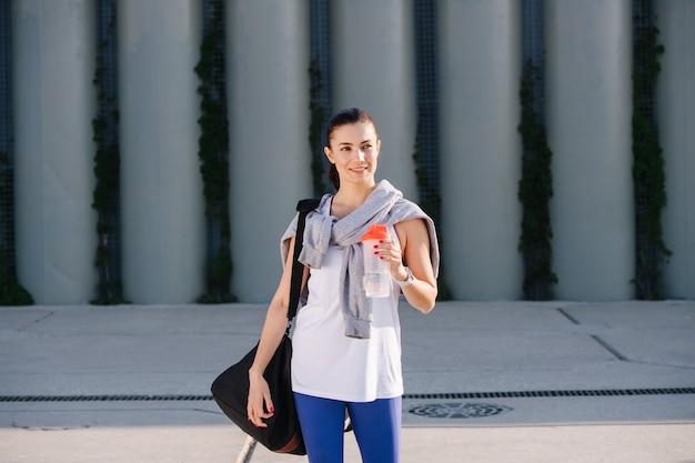 Urocza kobieta w sportowym stroju stojąca na ulicy trzymająca wodę